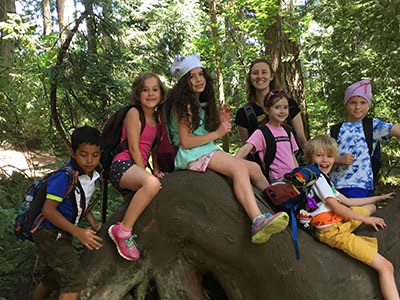 Photo of children climbing and sitting on a large tree root.