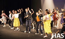 Hillsboro Arts Summer Camp students performing a musical on stage.