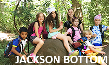Photo of five students sitting on an overgrown tree root with instructor standing in background.